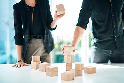 Buy stock photo Cropped shot of a businessman and businesswoman having a meeting with building blocks in a modern office