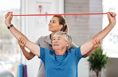Buy stock photo Shot of a young physiotherapist assisting a senior man with a resistance band