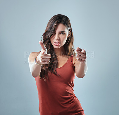Buy stock photo Studio portrait of a young woman pointing at the camera