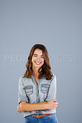 Buy stock photo Studio portrait of an attractive young woman standing with her arms crossed against a grey background