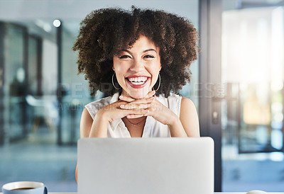 Buy stock photo Portrait of a cheerful young businesswoman seated at her and working on her laptop in the office during the day