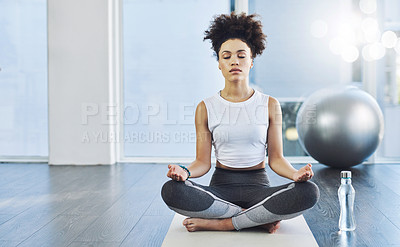 Buy stock photo Shot of a relaxed young woman practicing yoga while being seated on the floor inside of a yoga studio during the day