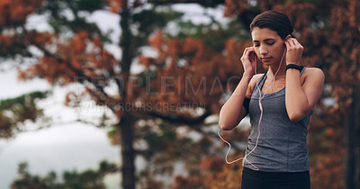Buy stock photo Shot of a young woman putting in her earphones before a run