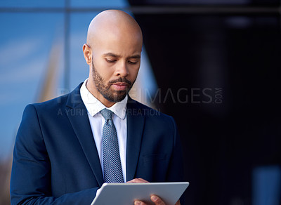 Buy stock photo Shot of a handsome young businessman using a digital tablet while standing outside an office building