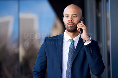 Buy stock photo Portrait of a handsome young businessman taking a phone call while standing outside an office building