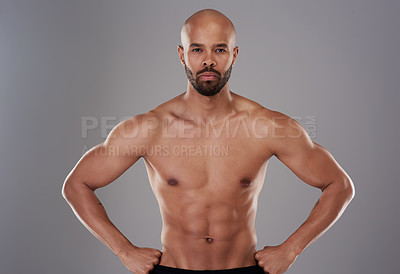 Buy stock photo Portrait of a handsome young athlete posing with his hands on his hips against a grey background