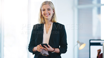 Buy stock photo Portrait of a confident young businesswoman holding her cellphone while standing inside of the office