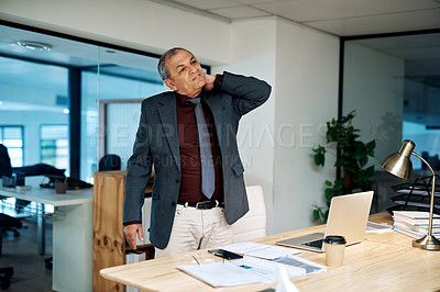 Buy stock photo Shot of a mature businessman suffering with neck pain while working in an office at night