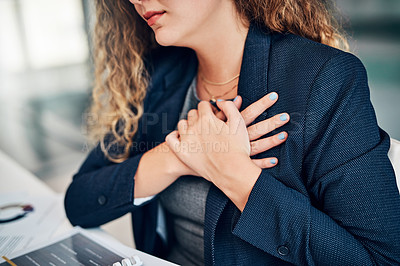 Buy stock photo Closeup shot of a businesswoman holding her chest in pain while working in an office