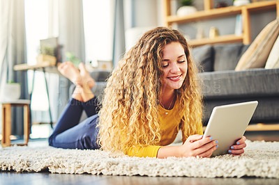 Buy stock photo Shot of a young woman using a digital tablet on the floor at home