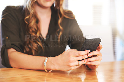 Buy stock photo Cropped shot of an unrecognizable young woman texting on her cellphone at home during the day