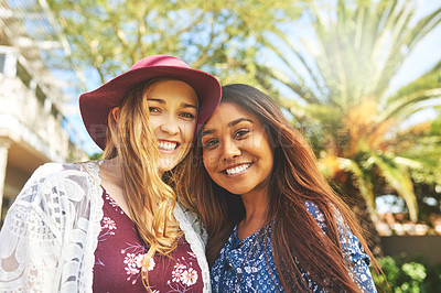 Buy stock photo Cropped shot of two cheerful young friends standing together outside during the day