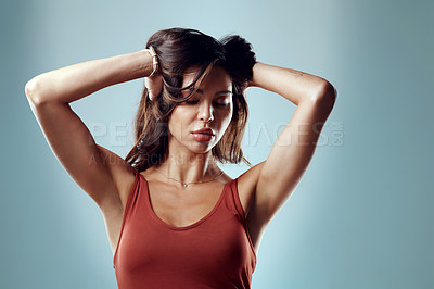 Buy stock photo Studio shot of an attractive young woman grabbing her  hair against a blue background