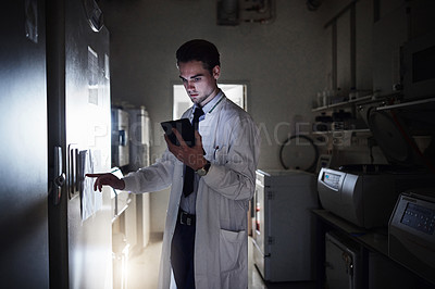 Buy stock photo Shot of a young scientist using a digital tablet while working in a laboratory at night