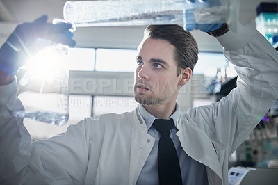 Buy stock photo Shot of a young scientist conducting an experiment with a beaker in a laboratory