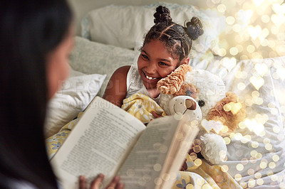 Buy stock photo Cropped shot of a woman reading her daughter a bedtime story