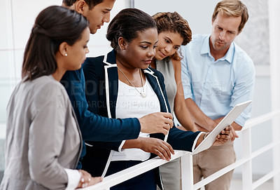 Buy stock photo Cropped shot of a diverse group of colleagues standing together and looking at a tablet in the office