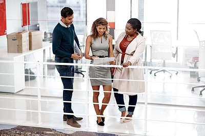Buy stock photo Full length shot of a diverse young group of colleagues at work discussing ideas on a tablet in the office