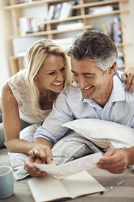 Buy stock photo Cropped shot of an affectionate mature couple lying on their living room floor looking at photographs