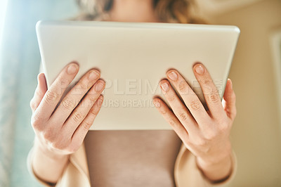 Buy stock photo Cropped shot of an unrecognizable young woman holding a digital tablet while standing indoors