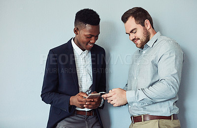 Buy stock photo Studio shot of two young businessmen using a smartphone together against a grey background