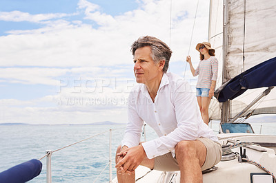 Buy stock photo Cropped shot of a handsome mature man enjoying a boat cruise out on the ocean with his wife in the background