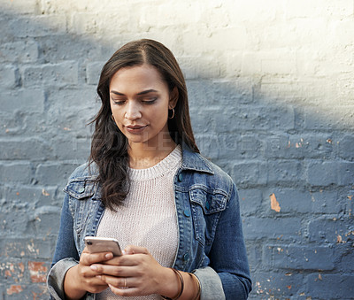 Buy stock photo Shot of an attractive young woman using her cellphone while out in the city