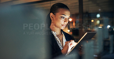 Buy stock photo Shot of a beautiful young businesswoman using a digital tablet while working late in her office during the evening