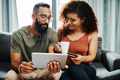 Buy stock photo Shot of a young couple using a credit card and digital tablet on the sofa at home