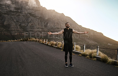 Buy stock photo Shot of a sporty young man standing with his arms outstretched while exercising outdoors
