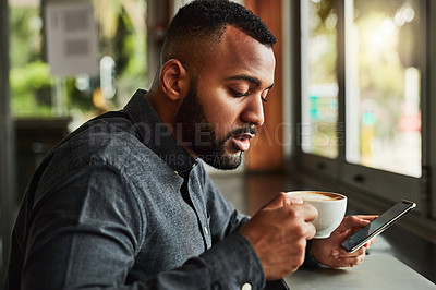 Buy stock photo Cropped shot of a young man using his cellphone while drinking coffee in a coffee shop