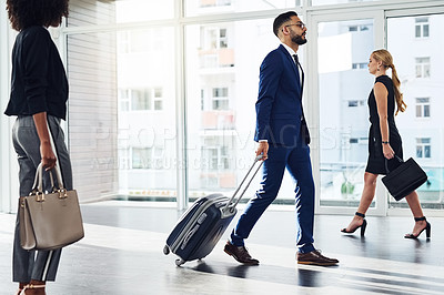 Buy stock photo Full length shot of businesspeople walking with their travel bags inside a building
