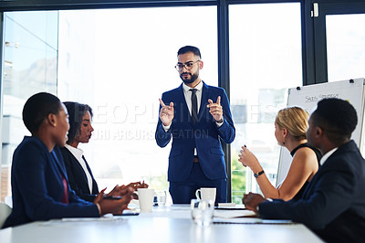 Buy stock photo Shot of a handsome young businessman explaining his ideas during a boardroom meeting with colleagues