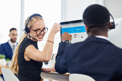 Buy stock photo Shot of two call centre agents giving each other a fist bump while working in an office