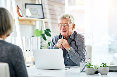 Buy stock photo Shot of a cheerful senior doctor during a consultation with a patient in his office
