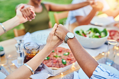 Buy stock photo Cropped shot of a group of unrecognizable friends joining hands to say grace at a dinner party outside in the afternoon