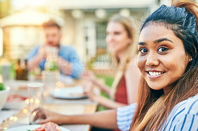 Buy stock photo Portrait of a cheerful young woman eating food at a dinner party with friends outside in the afternoon
