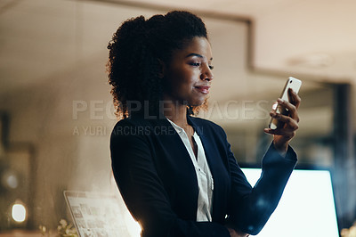 Buy stock photo Shot of a young businesswoman using a cellphone in an office at night
