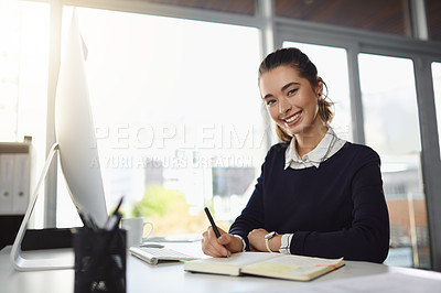 Buy stock photo Portrait of an attractive young businesswoman smiling and sitting at her desk while writing notes in a modern office