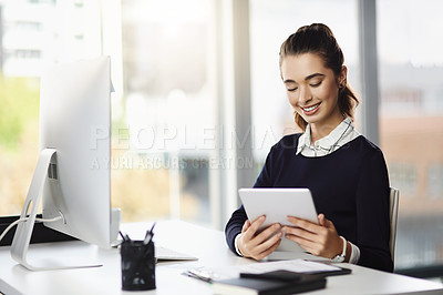 Buy stock photo Shot of an attractive young businesswoman sitting at her desk and using a tablet in a modern office