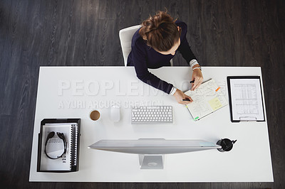 Buy stock photo Aerial shot of an unrecognizable young businesswoman sitting at her desk and writing notes in a modern office