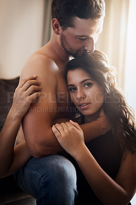 Buy stock photo Portrait of an affectionate young couple embracing while relaxing in their living room at home
