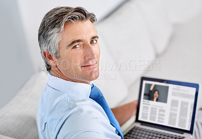 Buy stock photo Portrait of a confident mature businessman and sitting on a sofa while working on his laptop indoors
