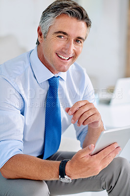 Buy stock photo Portrait of a confident mature businessman sitting on a sofa indoors while working on a tablet