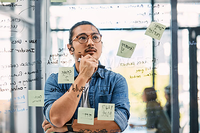 Buy stock photo Shot of a handsome young businessman planning and writing notes on a glass wall in his office