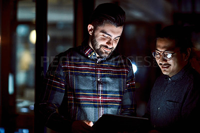 Buy stock photo Shot of two young businessmen using a digital tablet during a late night at work