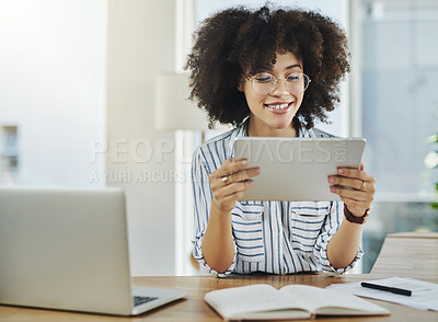 Buy stock photo Shot of an attractive young businesswoman using a digital tablet in her office at work