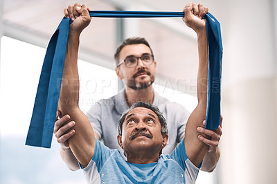 Buy stock photo Shot of a senior man exercising with a resistance band during a rehabilitation session with his physiotherapist