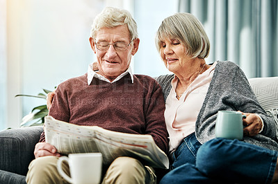 Buy stock photo Shot of a happy elderly couple reading the newspaper while relaxing together on the sofa at home