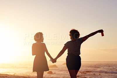 Buy stock photo Rearview shot of two unrecognizable young women holding hands and walking along the beach at sunset